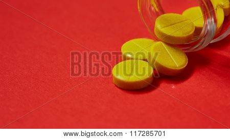 Pills spilling out of pill bottle on red. Top view with copy space.