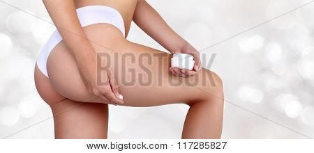Woman Hands Applying Moisturizer Cream On Thigh