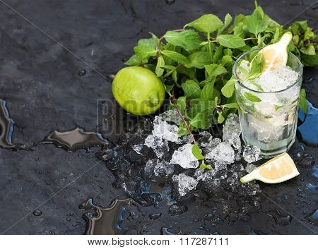 Mojito cooking set. Bunch of fresh mint, lime, chipped ice and coctail glass over black slate stone