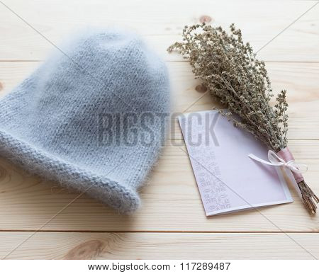 Soft Cap Of Blue Angora Bound By Hand On Natural Wooden Background With Beam Wormwood