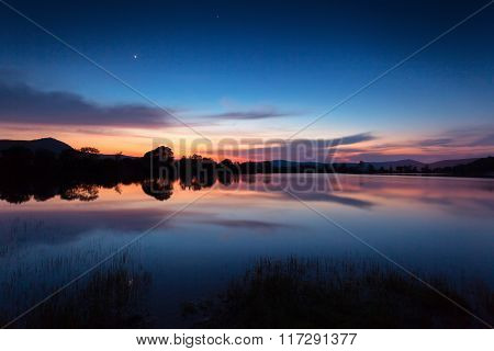 Mountain Lake With Stars And Reflected Clouds In Water. Night