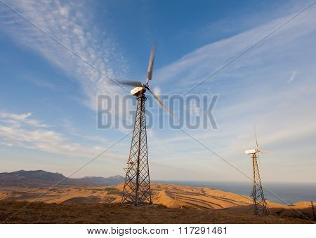 Wind Turbine Generating Electricity In Mountains At Sunset