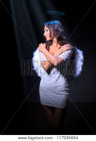 Young woman in an image of angel at dark room