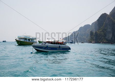 PHI PHI ISLANDS, THAILAND - CIRCA FEBRUARY, 2015: Speed boats with tourists engaged in diving and snorkelling in the Phi Phi Doh Island. Phi Phi Islands are popular among tourists from all over world