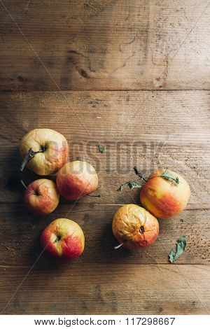 Decaying organic apples on wooden table
