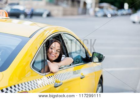 Young woman in yellow taxi