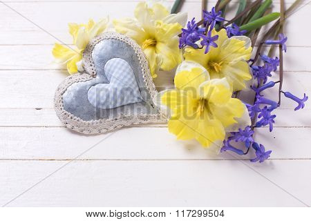 Yellow And Blue Spring Flowers And Decorative Heart  On White Wooden Planks.