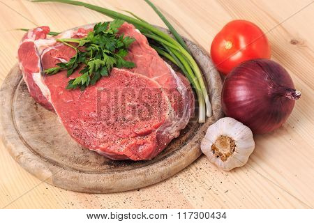 Slice Of Meat On The Cutting Board With Spices, Onion, Garlic And Green With Red Tomato