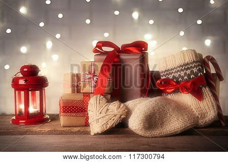 Pair of knitted socks with wrapped gifts for Christmas on light table