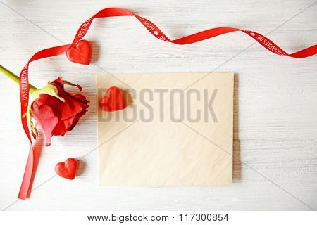 Beautiful rose with gift card on wooden background