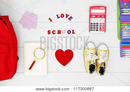 School set with backpack, shoes and supplies on light wooden background