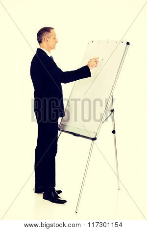 Male executive writing on a flipchart