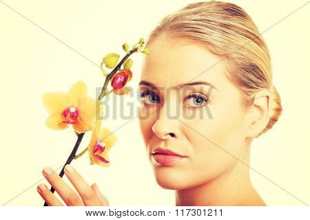 Beautiful spa woman with orange orchid