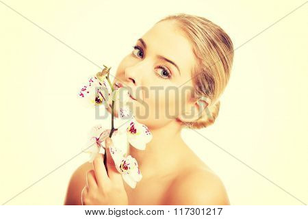 Topless woman with an orchid flower