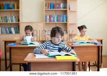 Classmates reading a book at school