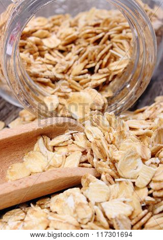 Oat Flakes Spilling Out Of Jar On Wooden Background