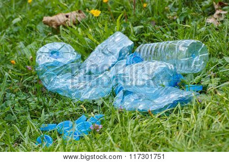 Plastic Bottles And Bottle Caps On Grass In Park, Littering Of Environment