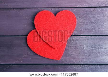 Red felt hearts on purple wooden background
