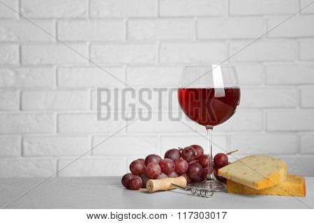 Red wine with grape and cheese on brick wall background