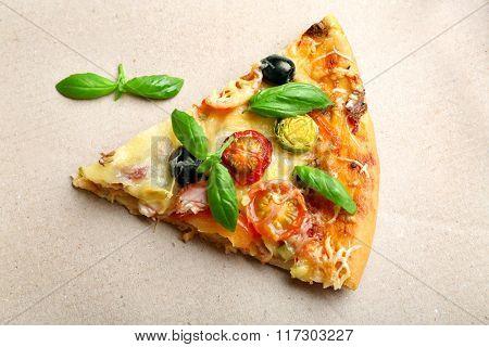 Piece of fresh pizza on cardboard closeup
