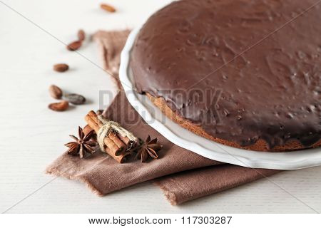 Tasty chocolate frosting cake on light table, close up