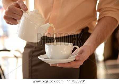 Waiter pouring tea into cup close up