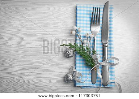 Christmas serving cutlery with a napkin over light wooden table