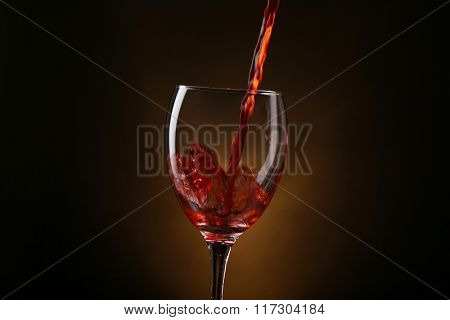 Wine pouring in glass on brown background