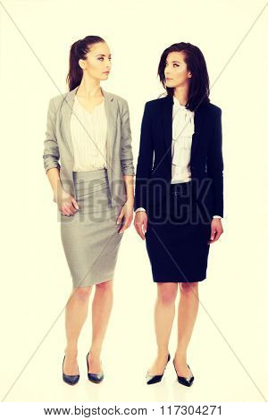 Two women in office outfits looking at each other.