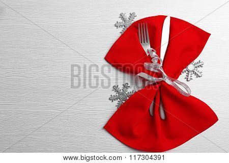 Christmas serving cutlery in a napkin over light wooden table