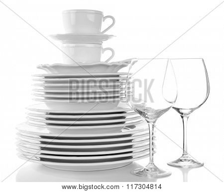 Stack of plates, cups and wineglasses on white background