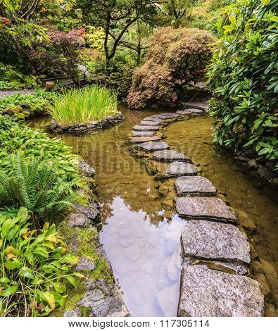 The track of  stones in Japanese part of garden. Beautiful decorative private garden in western Canada - Butchart Gardens
