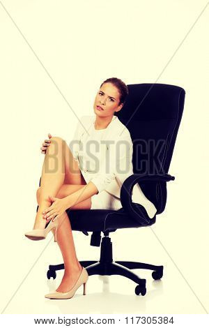 Businesswoman with leg pain sitting on the armchair