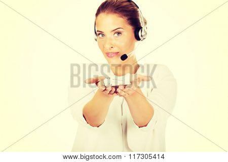 Young businesswoman in headset holding plane toy