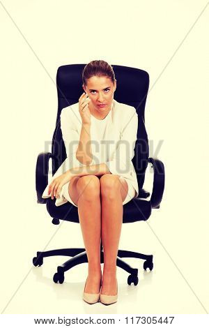 Depressed businesswoman sitting on armchair