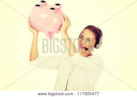Young businesswoman in headset holding piggybank
