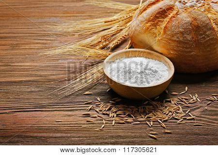 Fresh baked bread, a bowl of flour and wheat ears on the wooden background