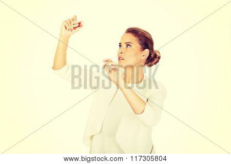 Young businesswoman writes something big pen