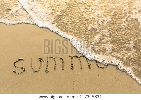 Summer - inscription on sand beach with the soft wave.