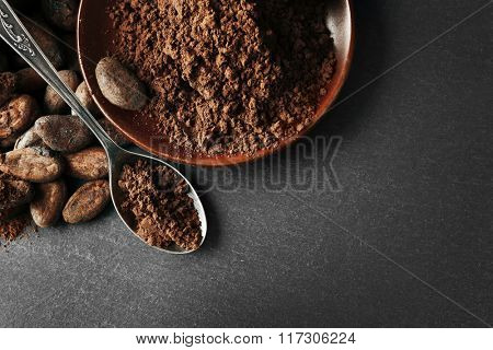 Bowl with aromatic cocoa beans and chocolate on grey background, close up