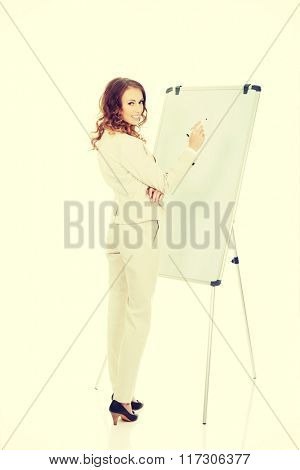 Business woman writing on flipchart.