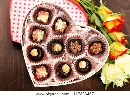 Heart shaped box with candies and flowers on a wooden background, close up