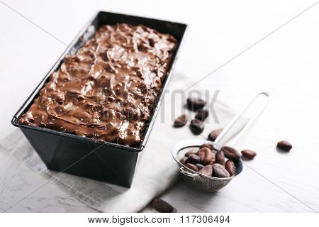 Delicious chocolate cake with nut cream in pan on white wooden table, close up