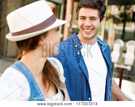Happy young couple walking in city