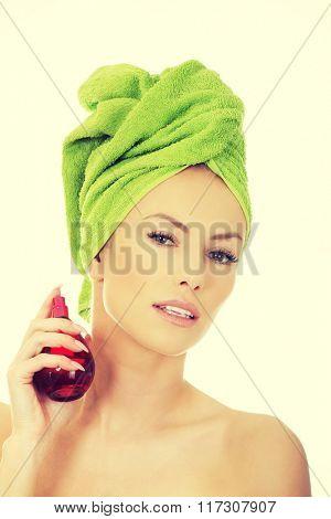 Beautiful woman applying perfume.