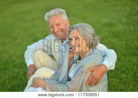 Elderly couple sitting on grass