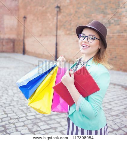 Young attractive happy shopper woman wearing hat and glasses holding shopping bags  walking in the street