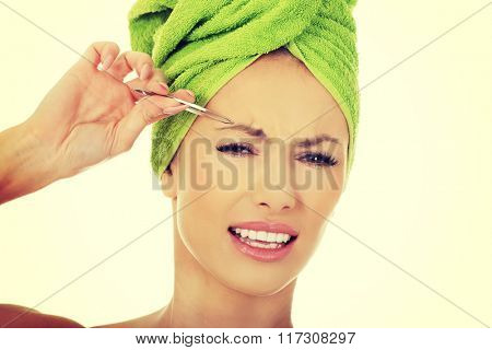 Beautiful woman plucking her eyebrow.