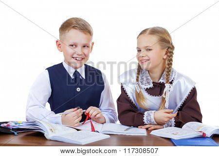 A couple of elementary school students sit at a desk, isolated on white