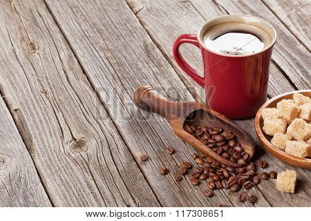 Coffee cup, beans and brown sugar on wooden table. View with copy space